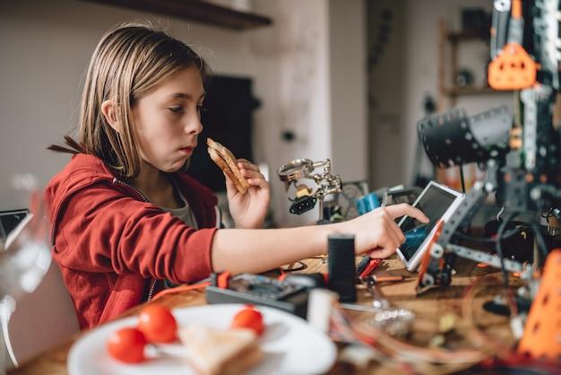 サンドイッチを食べたり、タブレットを使用して赤いパーカーを着ている少女 Premium写真