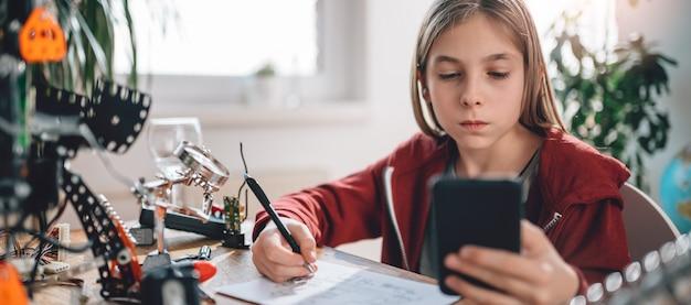 Девушка с помощью смарт-телефона, чтобы проверить электрическую схему Premium Фотографии
