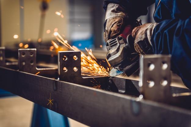 Рабочий, использующий угловую шлифовальную машину Premium Фотографии