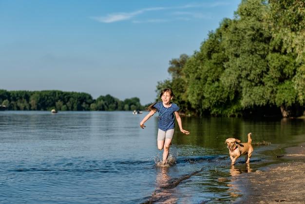 川で彼女の犬と遊ぶ少女 Premium写真