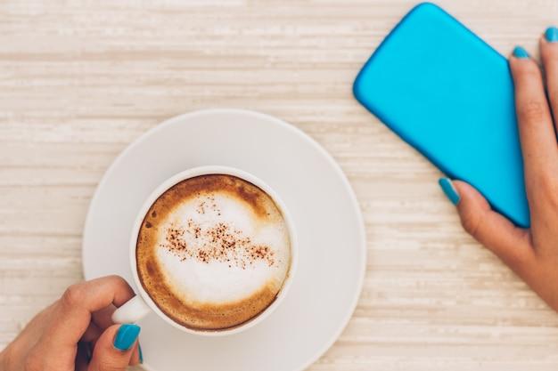 必要なもの:コーヒーカップとスマートフォン Premium写真