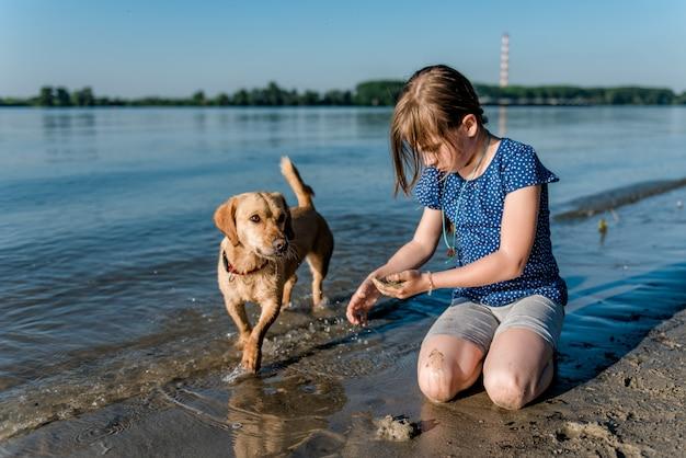 ビーチで遊ぶ犬を持つ少女 Premium写真