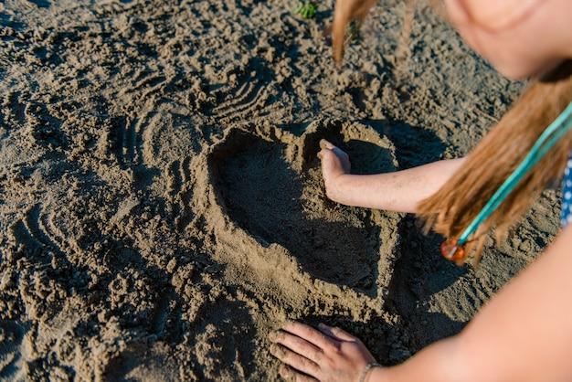 Девушка делает сердце из песка Premium Фотографии