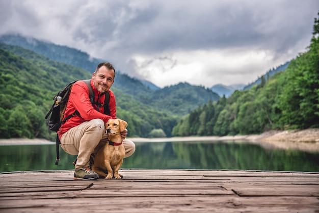 桟橋のポーズで犬とハイカー Premium写真