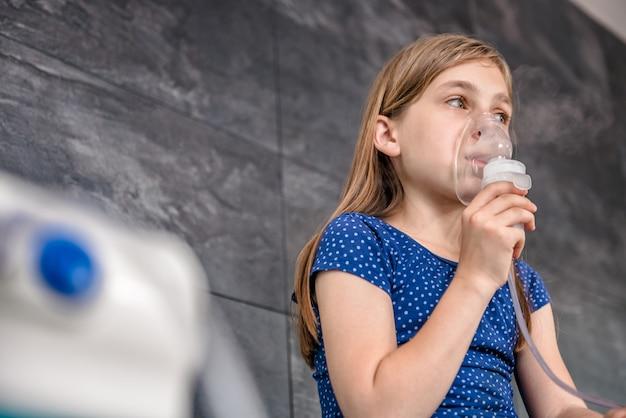 Маленькая девочка с медицинской ингаляции с помощью небулайзера Premium Фотографии