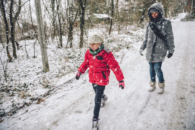 雪に覆われた森でのハイキングの娘を持つ母 Premium写真