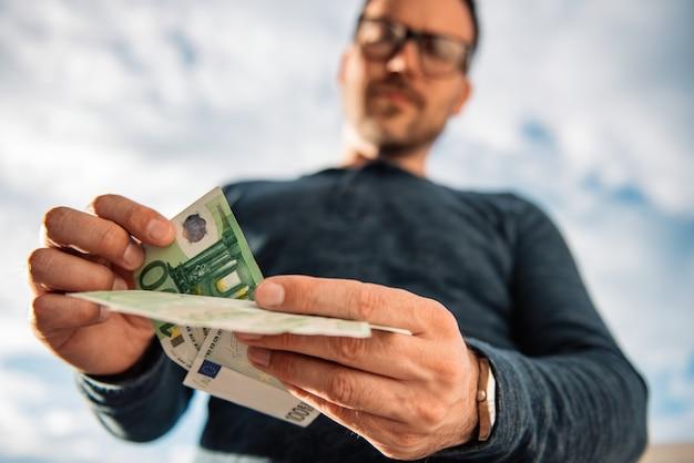 お金を数える男 Premium写真