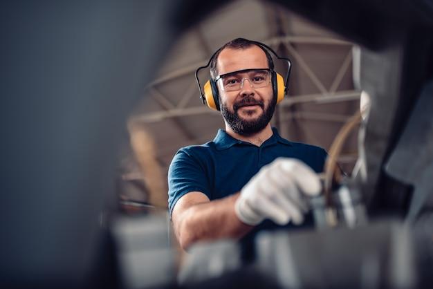 Заводской рабочий работает ленточнопильный станок Premium Фотографии