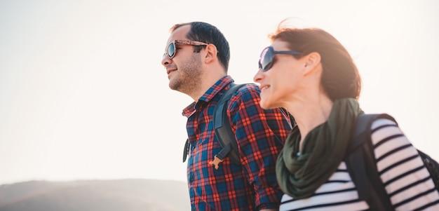 幸せなカップルが山で一緒にハイキング Premium写真