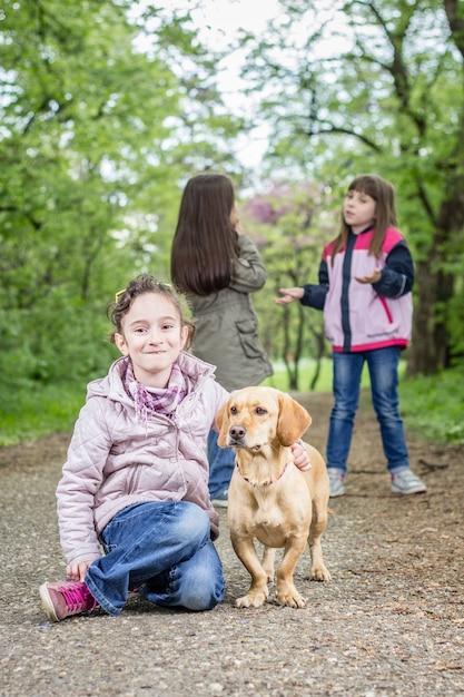 Девочка и собака в парке Premium Фотографии