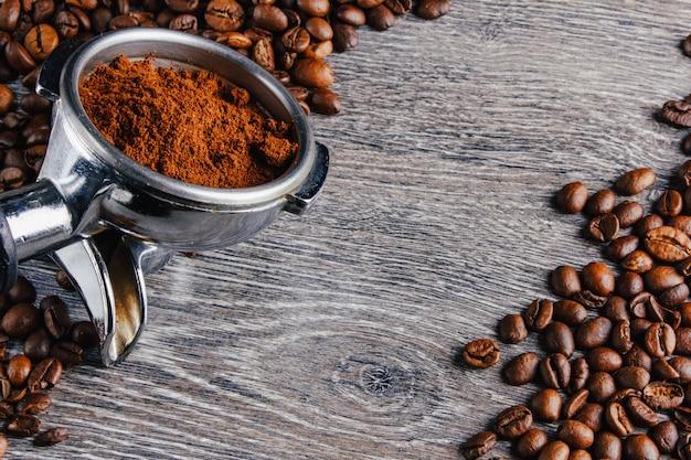 Портафильтр и кофейные зерна на фоне дерева Premium Фотографии
