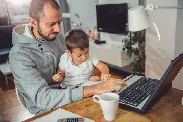 Отец работает на ноутбуке и держит сына на коленях Premium Фотографии