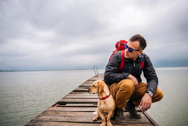 ドックに座っている彼の犬を持つ男 Premium写真