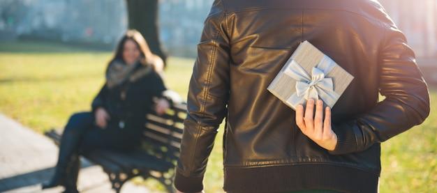 Мужчина держит подарок за спиной Premium Фотографии