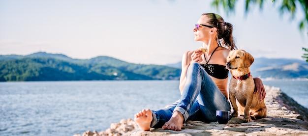 女性と一緒に太陽を楽しんでいる彼女の犬 Premium写真