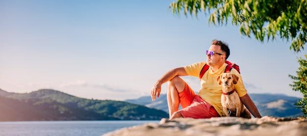 男と犬は石のドックに座って、太陽の光を楽しんで Premium写真
