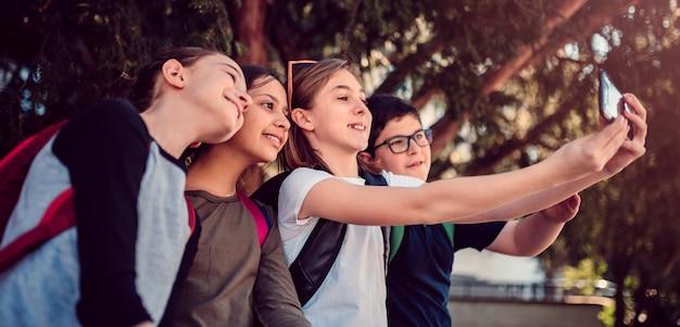 Школьники сидят в тени и принимают селфи на улице Premium Фотографии