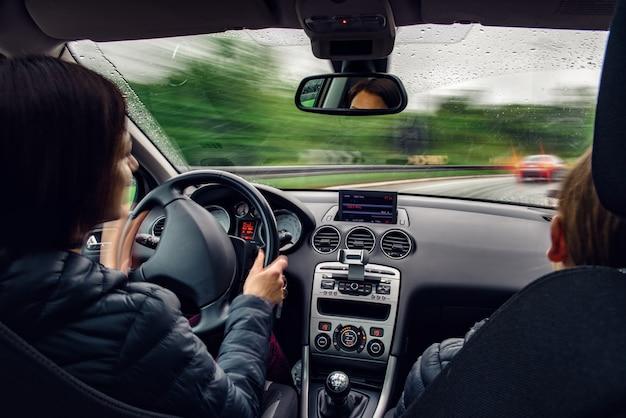 雨の中で角を曲がった車を運転する女性 Premium写真