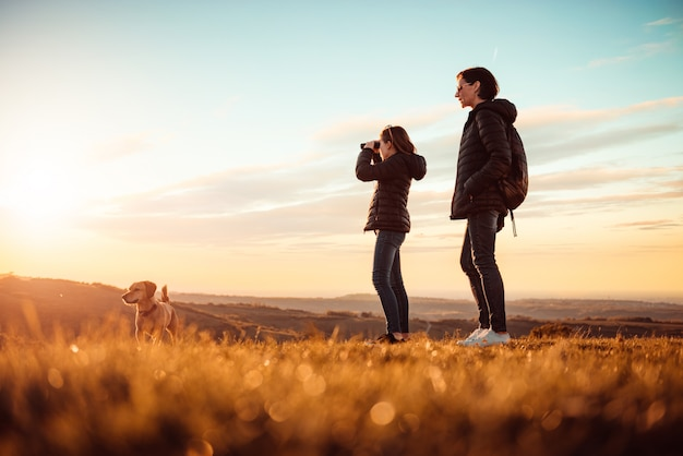 母と娘の犬と山の上に立って、双眼鏡を使用して Premium写真