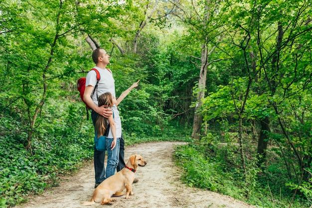 父と娘が犬と森の中を歩く Premium写真