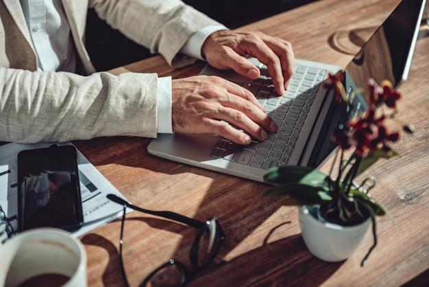 彼の机に座って、オフィスでラップトップを使用しての実業家 Premium写真