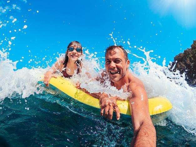 父と娘がエアベッドに浮かんでいる間、ビーチで楽しんで Premium写真