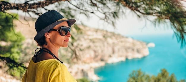 ツリーの下の崖の上に立って、海を探している女性 Premium写真