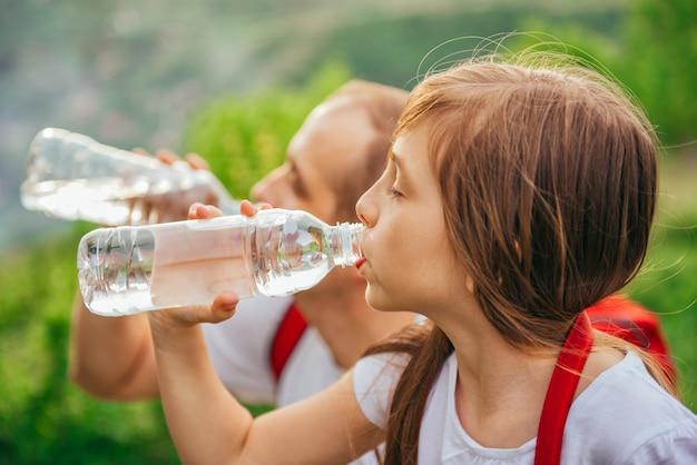 Отец и дочь пьют воду Premium Фотографии