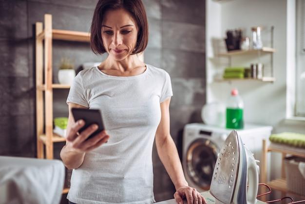 女性が服をアイロンしながらスマートフォンを使用して Premium写真