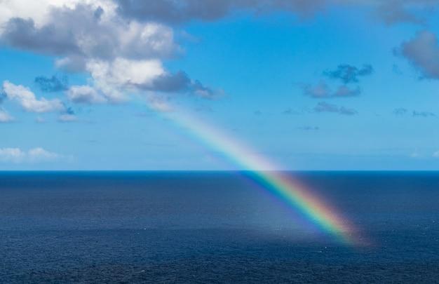 Радуга в атлантическом океане, с голубым небом и облаками Premium Фотографии
