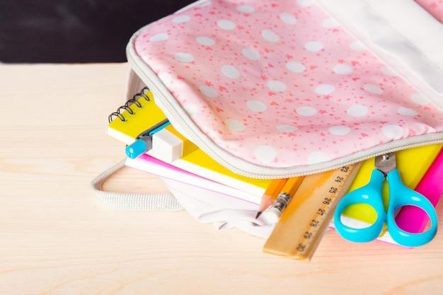 学校用品を備えた明るいオープンスクールバッグは、学校の黒板を背景に机の上にあります。 Premium写真