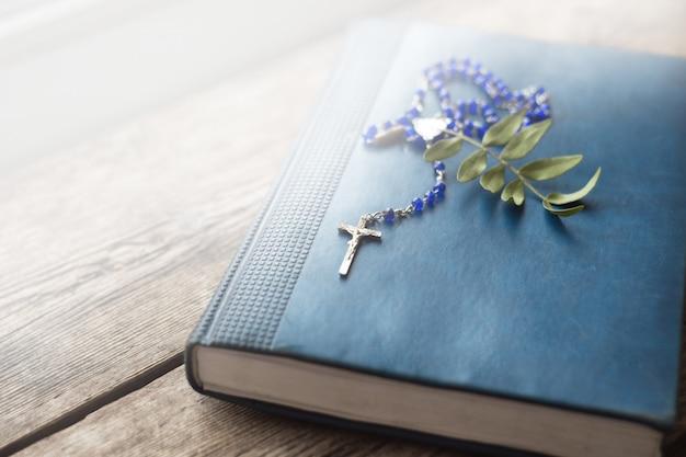 Крест на античной библии на деревянном столе. святой бо Premium Фотографии