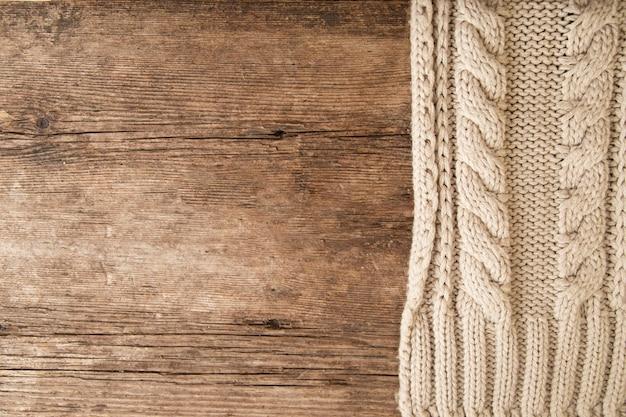 木製の背景にベージュのニットセーターのテクスチャ。ニット、クローズアップ Premium写真