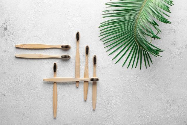 廃棄物ゼロ、生分解性の竹製歯ブラシ、灰色の石のコンクリートのカウンタートップ、側面に緑のヤシの葉。地球、エコロジー、エコを救うというコンセプト Premium写真