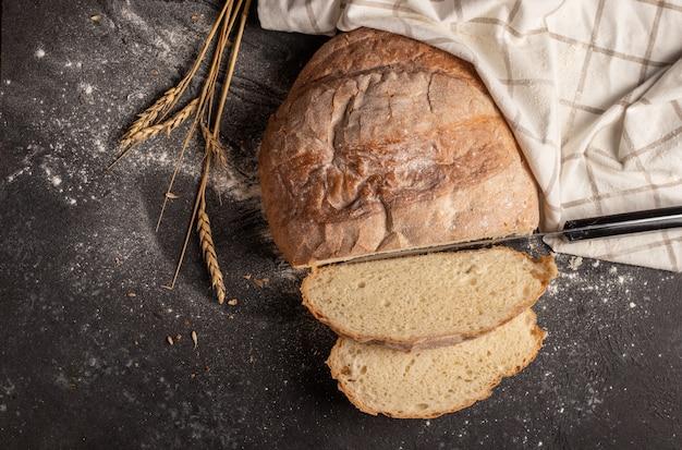 Белый хлеб нарезанный на кусочки с белой клетчатой салфеткой и колосками пшеницы на черном Premium Фотографии