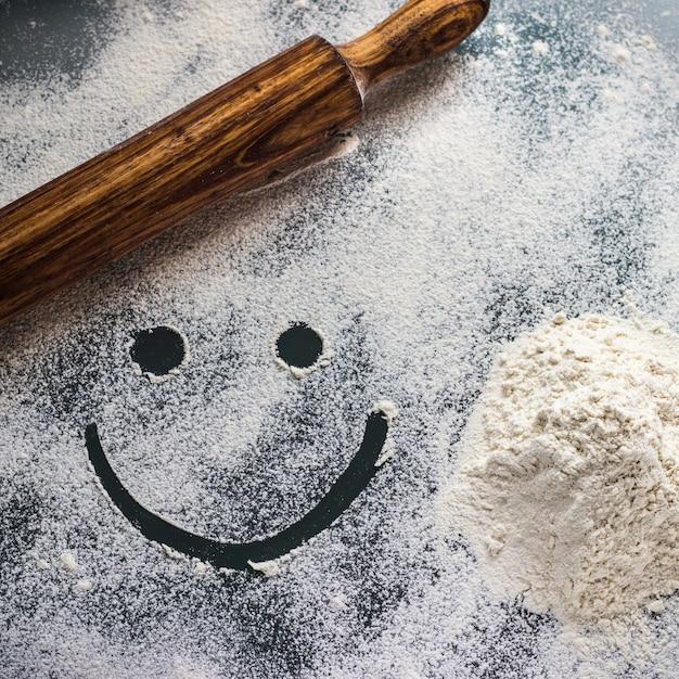 小麦粉、麺棒、スマイリーの顔を持つ作業テーブル。 Premium写真