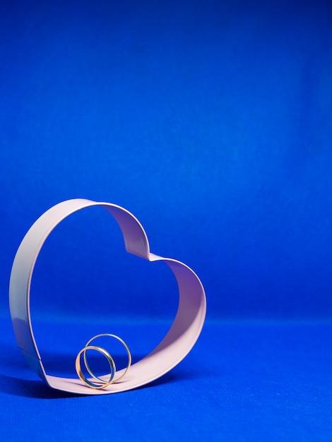 ハート型のクッキー型フレーム。中央の結婚指輪。青色の背景、分離、メッセージ用のスペースをコピーします。バレンタインデーのコンセプト愛の宣言。 Premium写真