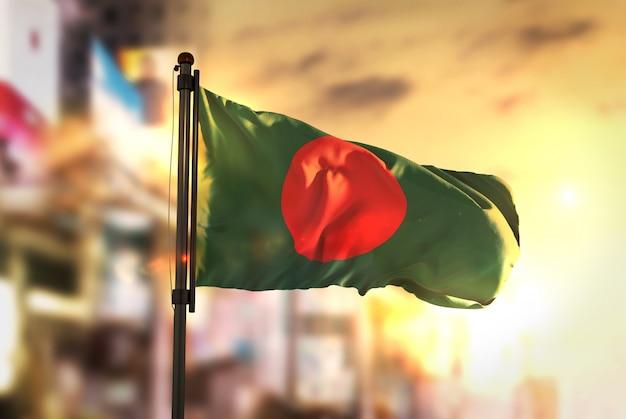 Бангладеш флаг против города размытый фон при восходе солнца Premium Фотографии