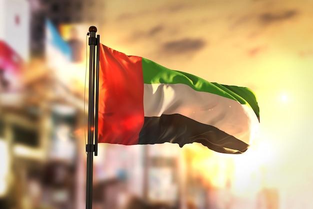 アラブ首長国連邦の国旗は、日の出のバックライトで街をぼやけた Premium写真