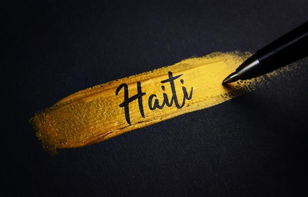 Текст рукописного ввода гаити на золотой кисти Premium Фотографии