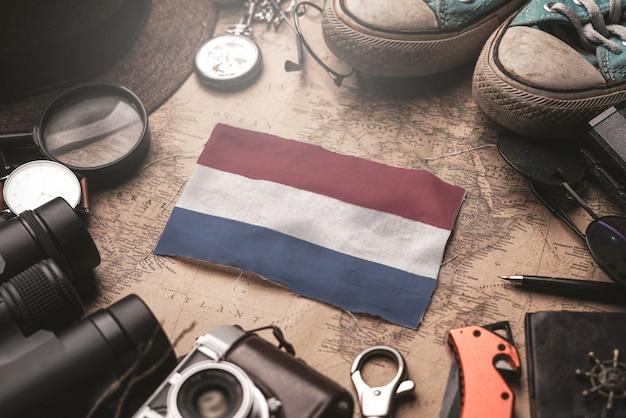 古いビンテージ地図上の旅行者のアクセサリー間のオランダ国旗。観光地のコンセプト。 Premium写真