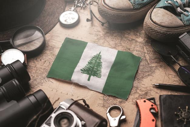古いビンテージ地図上の旅行者のアクセサリーの間にノーフォーク島の旗。観光地のコンセプト。 Premium写真