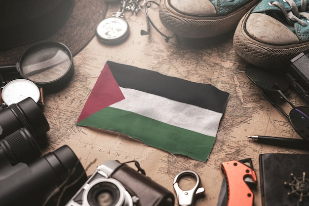 古いビンテージ地図上の旅行者のアクセサリー間のパレスチナの旗。観光地のコンセプト。 Premium写真