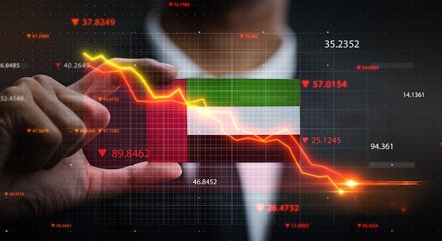 アラブ首長国連邦の旗の前で落ちるグラフ。危機の概念 Premium写真