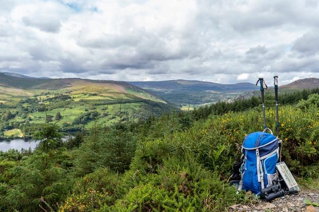 Рюкзак, бинокль, карта и палки на горе, горный образ жизни в ирландии. Premium Фотографии