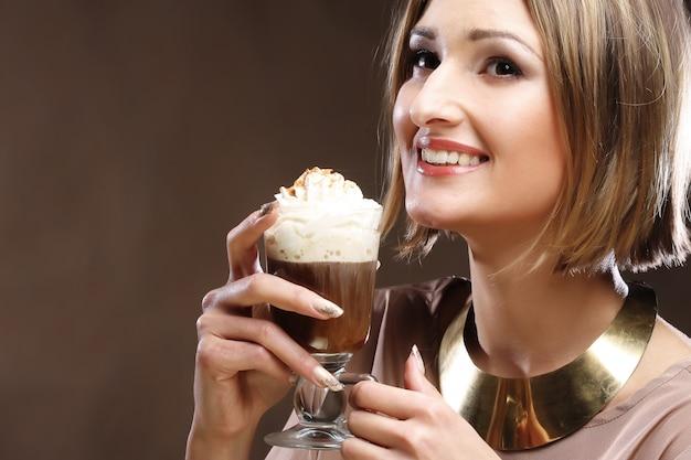 ホイップクリームとコーヒーのグラスを持つ女性 Premium写真