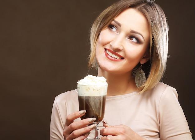 クリームとコーヒーのグラスを持つ少女 Premium写真