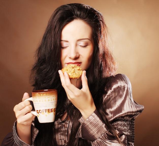 Женщина с кофе и печеньем Premium Фотографии