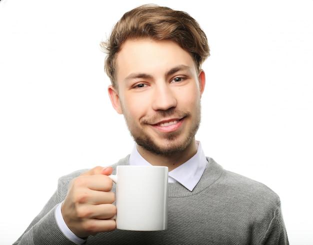 Портрет красивого молодого человека с чашкой, изолированный на белизне. Premium Фотографии