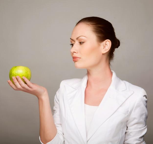 リンゴを保持している幸せな健康な女性 Premium写真